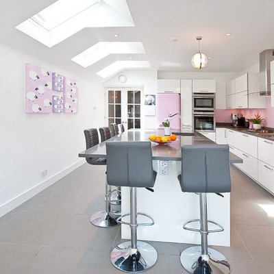 Inspiration for a contemporary l-shaped kitchen remodel in Surrey with an undermount sink, flat-panel cabinets, white cabinets, pink backsplash, glass sheet backsplash, colored appliances and an island