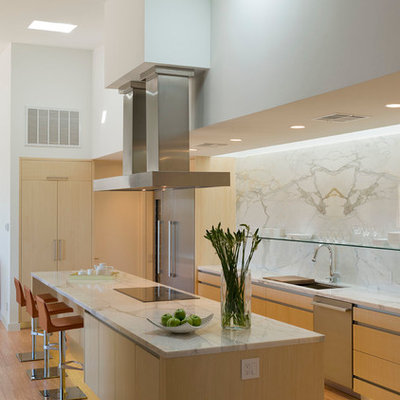 Example of a minimalist u-shaped kitchen design in Austin with an undermount sink, flat-panel cabinets, light wood cabinets, stainless steel appliances and marble backsplash