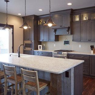Idee per una grande cucina abitabile minimalista con lavello sottopiano, ante lisce, ante marroni, top in quarzite, elettrodomestici in acciaio inossidabile, pavimento in legno massello medio e isola