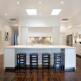 ブリスベンの広いコンテンポラリースタイルのおしゃれなキッチン (フラットパネル扉のキャビネット、白いキャビネット、グレーのキッチンパネル、ガラス板のキッチンパネル、シルバーの調理設備、濃色無垢フローリング、ダブルシンク、クオーツストーンカウンター) の写真