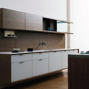 Diseño de cocina de galera, minimalista, con encimera de acrílico, fregadero bajoencimera, armarios con paneles lisos, puertas de armario blancas y salpicadero marrón