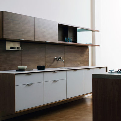 Example of a minimalist galley kitchen design in New York with solid surface countertops, an undermount sink, flat-panel cabinets, white cabinets and brown backsplash
