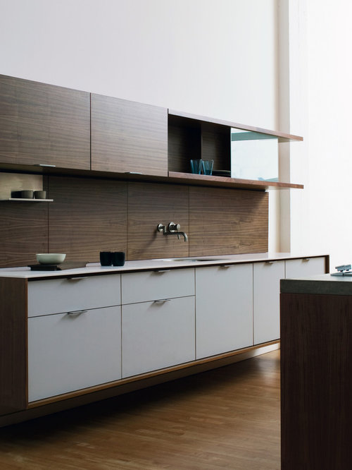 Example of a minimalist galley kitchen design in New York with solid  surface countertops, an