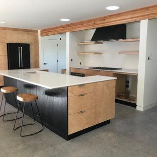 Große Moderne Küche in U-Form mit Vorratsschrank, Unterbauwaschbecken, flächenbündigen Schrankfronten, hellen Holzschränken, Quarzwerkstein-Arbeitsplatte, schwarzen Elektrogeräten, Betonboden, Kücheninsel, grauem Boden, weißer Arbeitsplatte und freigelegten Dachbalken in San Luis Obispo
