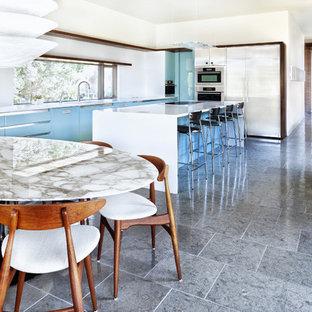 Bild på ett funkis kök och matrum, med rostfria vitvaror, släta luckor, turkosa skåp och bänkskiva i kvarts