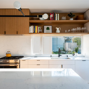 Enclosed kitchen - mid-sized contemporary galley medium tone wood floor and brown floor enclosed kitchen idea in Seattle with an undermount sink, flat-panel cabinets, white cabinets, quartz countertops, white backsplash, marble backsplash, paneled appliances, an island and white countertops