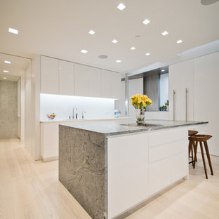 This is an example of a modern l-shaped kitchen in New York with an undermount sink, flat-panel cabinets, white cabinets, marble benchtops, white splashback, stone slab splashback, light hardwood floors, with island, green benchtop, panelled appliances and beige floor.