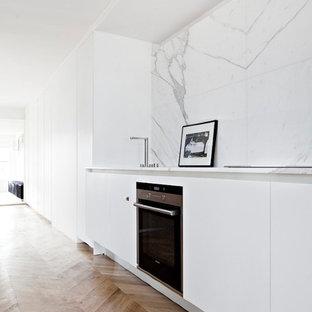 Idées déco pour une cuisine ouverte linéaire moderne de taille moyenne avec des portes de placard blanches, un plan de travail en marbre, une crédence blanche, un sol en bois brun, aucun îlot, un placard à porte plane, un électroménager noir et une crédence en marbre.