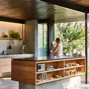 Inspiration for a small contemporary galley kitchen in Brisbane with an undermount sink, flat-panel cabinets, light wood cabinets, granite benchtops, concrete floors, with island, grey floor and black benchtop.