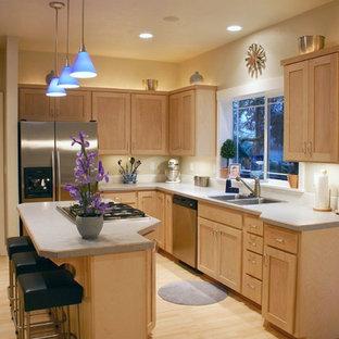 На фото: угловая кухня среднего размера в классическом стиле с столешницей из ламината, накладной раковиной, фасадами в стиле шейкер, светлыми деревянными фасадами, белым фартуком, фартуком из керамогранитной плитки, техникой из нержавеющей стали, полом из бамбука и островом