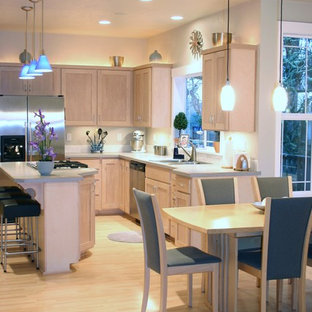 Photo of a mid-sized traditional l-shaped eat-in kitchen in Portland with a drop-in sink, shaker cabinets, light wood cabinets, laminate benchtops, stainless steel appliances, bamboo floors, with island, beige splashback and porcelain splashback.