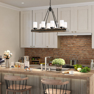 Inspiration for a small country u-shaped kitchen/diner in Atlanta with a double-bowl sink, beaded cabinets, beige cabinets, concrete worktops, beige splashback, brick splashback, stainless steel appliances, plywood flooring, an island, brown floors and white worktops.