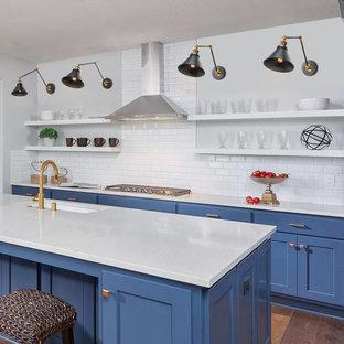 Пример оригинального дизайна: маленькая отдельная, параллельная кухня в стиле модернизм с врезной раковиной, фасадами с декоративным кантом, синими фасадами, деревянной столешницей, белым фартуком, фартуком из керамической плитки, техникой из нержавеющей стали, темным паркетным полом, островом, коричневым полом и синей столешницей