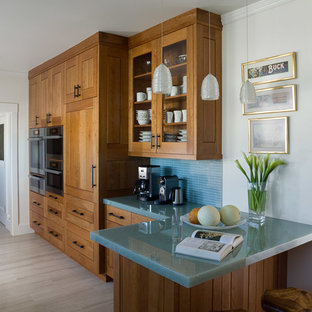 This is an example of a mid-sized contemporary galley separate kitchen in San Francisco with a double-bowl sink, shaker cabinets, medium wood cabinets, glass benchtops, blue splashback, matchstick tile splashback, stainless steel appliances, porcelain floors, a peninsula and turquoise benchtop.