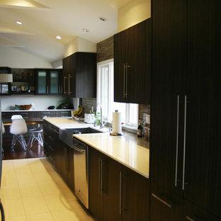 Пример оригинального дизайна: большая параллельная кухня в стиле модернизм с обеденным столом, раковиной в стиле кантри, плоскими фасадами, темными деревянными фасадами, столешницей из кварцевого композита, разноцветным фартуком, фартуком из стеклянной плитки, техникой из нержавеющей стали, полом из бамбука и полуостровом