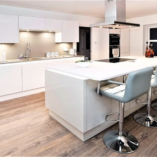 Photo of a modern kitchen in Other with a built-in sink, flat-panel cabinets, white cabinets, beige splashback, black appliances, medium hardwood flooring, an island, brown floors and white worktops.