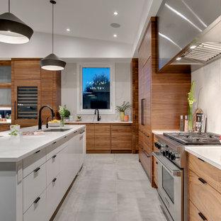 カルガリーの大きいモダンスタイルのおしゃれなキッチン (アンダーカウンターシンク、フラットパネル扉のキャビネット、中間色木目調キャビネット、クオーツストーンカウンター、白いキッチンパネル、大理石の床、パネルと同色の調理設備、セラミックタイルの床、グレーの床、白いキッチンカウンター) の写真