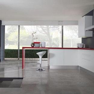 Geschlossene, Große Moderne Küche in L-Form mit flächenbündigen Schrankfronten, weißen Schränken, Laminat-Arbeitsplatte, Küchengeräten aus Edelstahl, Betonboden, Halbinsel, grauem Boden und roter Arbeitsplatte in Miami