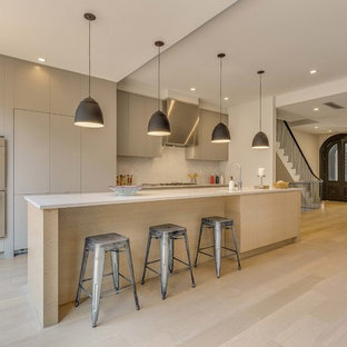 Kitchen - modern galley light wood floor and beige floor kitchen idea in New York with flat-panel cabinets, gray cabinets, stainless steel appliances, an island and white countertops