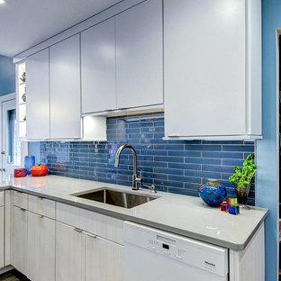 フィラデルフィアの中くらいのモダンスタイルのおしゃれなキッチン (アンダーカウンターシンク、フラットパネル扉のキャビネット、白いキャビネット、珪岩カウンター、青いキッチンパネル、ガラスタイルのキッチンパネル、パネルと同色の調理設備、クッションフロア、グレーの床、グレーのキッチンカウンター) の写真