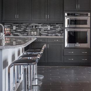 ジャクソンビルの広いモダンスタイルのおしゃれなキッチン (エプロンフロントシンク、フラットパネル扉のキャビネット、黒いキャビネット、御影石カウンター、マルチカラーのキッチンパネル、セラミックタイルのキッチンパネル、シルバーの調理設備、セラミックタイルの床) の写真