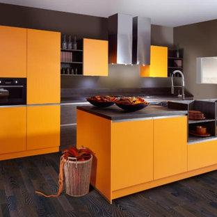 Свежая идея для дизайна: параллельная кухня среднего размера в стиле модернизм с обеденным столом, раковиной в стиле кантри, плоскими фасадами, оранжевыми фасадами, столешницей из акрилового камня, темным паркетным полом, островом и техникой под мебельный фасад - отличное фото интерьера