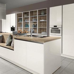 トロントの大きいモダンスタイルのおしゃれなキッチン (トリプルシンク、フラットパネル扉のキャビネット、白いキャビネット、木材カウンター、磁器タイルの床、パネルと同色の調理設備) の写真