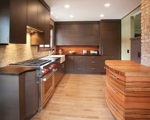 modern lshaped kitchen idea in milwaukee with paneled appliances wood countertops a