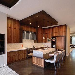 Modern inredning av ett mellanstort kök, med en undermonterad diskho, släta luckor, skåp i mellenmörkt trä, marmorbänkskiva, vitt stänkskydd, rostfria vitvaror, mörkt trägolv och en köksö