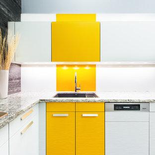 トロントのコンテンポラリースタイルのおしゃれなキッチン (アンダーカウンターシンク、フラットパネル扉のキャビネット、黄色いキャビネット、人工大理石カウンター、白いキッチンパネル、パネルと同色の調理設備) の写真