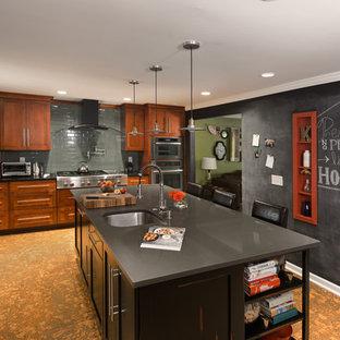 他の地域の広いエクレクティックスタイルのおしゃれなキッチン (エプロンフロントシンク、シェーカースタイル扉のキャビネット、中間色木目調キャビネット、クオーツストーンカウンター、グレーのキッチンパネル、シルバーの調理設備、コルクフローリング、ガラスタイルのキッチンパネル) の写真