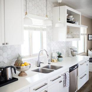 Esempio di una piccola cucina moderna con lavello a doppia vasca, nessun'anta, ante bianche, top in quarzo composito, paraspruzzi bianco, paraspruzzi in marmo, elettrodomestici in acciaio inossidabile, pavimento in laminato, nessuna isola, pavimento beige e top bianco