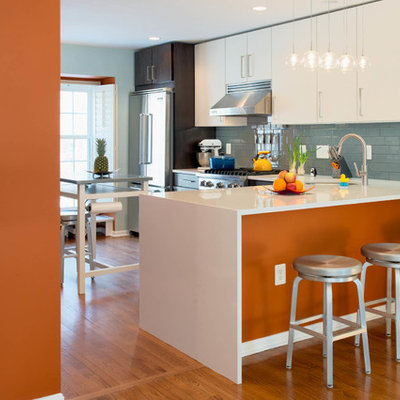 Mid-sized trendy galley medium tone wood floor eat-in kitchen photo in DC Metro with flat-panel cabinets, white cabinets, blue backsplash, an undermount sink, ceramic backsplash, stainless steel appliances and an island
