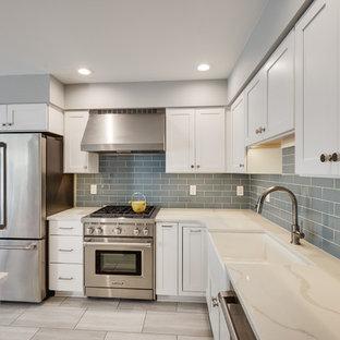 Modern inredning av ett avskilt, litet vit vitt l-kök, med en rustik diskho, luckor med infälld panel, vita skåp, bänkskiva i kvarts, blått stänkskydd, stänkskydd i glaskakel, rostfria vitvaror, vinylgolv, en köksö och beiget golv