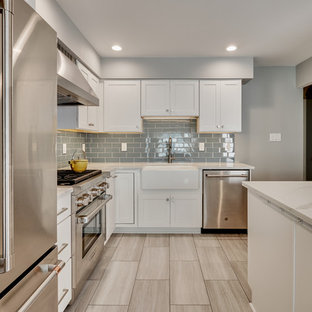 Enclosed kitchen - small modern l-shaped vinyl floor and beige floor enclosed kitchen idea in Philadelphia with a farmhouse sink, recessed-panel cabinets, white cabinets, quartz countertops, blue backsplash, glass tile backsplash, stainless steel appliances, an island and white countertops