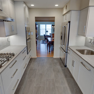 Mid-sized modern enclosed kitchen designs - Enclosed kitchen - mid-sized modern galley enclosed kitchen idea in DC Metro with an undermount sink, shaker cabinets, gray cabinets, quartz countertops, beige backsplash, stainless steel appliances and a peninsula