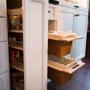 Modelo de cocina moderna con fregadero bajoencimera, armarios con paneles empotrados, puertas de armario blancas, encimera de esteatita, salpicadero de azulejos de vidrio, electrodomésticos de acero inoxidable, suelo de madera en tonos medios y una isla