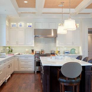 Foto på ett vintage vit kök, med vita skåp, en köksö, luckor med profilerade fronter, mörkt trägolv, rostfria vitvaror, en undermonterad diskho, marmorbänkskiva, vitt stänkskydd och stänkskydd i mosaik