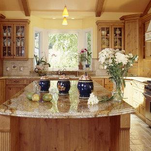 ロサンゼルスの大きいサンタフェスタイルのおしゃれなキッチン (アンダーカウンターシンク、シェーカースタイル扉のキャビネット、中間色木目調キャビネット、御影石カウンター、ベージュキッチンパネル、石タイルのキッチンパネル、シルバーの調理設備の) の写真
