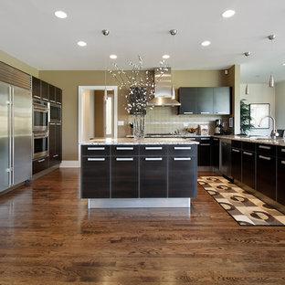 ワシントンD.C.の大きいモダンスタイルのおしゃれなキッチン (フラットパネル扉のキャビネット、黒いキャビネット、御影石カウンター、黄色いキッチンパネル、セラミックタイルのキッチンパネル、シルバーの調理設備の、濃色無垢フローリング、マルチカラーのキッチンカウンター) の写真