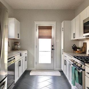 シンシナティの小さいモダンスタイルのおしゃれなII型キッチン (アンダーカウンターシンク、シェーカースタイル扉のキャビネット、白いキャビネット、珪岩カウンター、黄色いキッチンパネル、セラミックタイルのキッチンパネル、シルバーの調理設備、セラミックタイルの床、黒い床、ベージュのキッチンカウンター) の写真