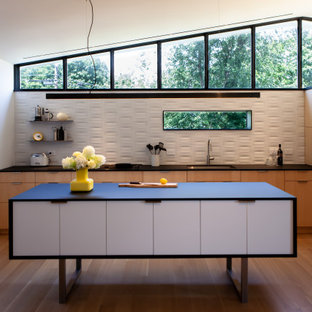 Inspiration for a mid-sized midcentury l-shaped open plan kitchen in New York with an undermount sink, flat-panel cabinets, light wood cabinets, laminate benchtops, white splashback, ceramic splashback, black appliances, light hardwood floors, with island and black benchtop.
