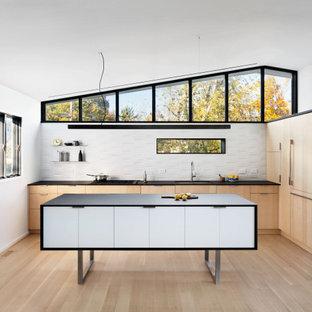 ニューヨークのコンテンポラリースタイルのおしゃれなアイランドキッチン (アンダーカウンターシンク、フラットパネル扉のキャビネット、淡色木目調キャビネット、ラミネートカウンター、白いキッチンパネル、セラミックタイルのキッチンパネル、黒い調理設備、淡色無垢フローリング、黒いキッチンカウンター、三角天井) の写真