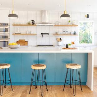 サンフランシスコの中サイズのコンテンポラリースタイルのおしゃれなキッチン (アンダーカウンターシンク、フラットパネル扉のキャビネット、白いキャビネット、クオーツストーンカウンター、白いキッチンパネル、磁器タイルのキッチンパネル、シルバーの調理設備の、無垢フローリング、ベージュの床、グレーのキッチンカウンター) の写真