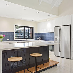 Design ideas for a contemporary l-shaped kitchen in Gold Coast - Tweed with an undermount sink, flat-panel cabinets, white cabinets, blue splashback, stainless steel appliances, with island and white floor.