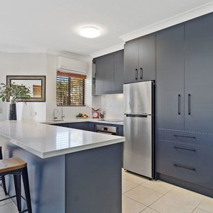 This is an example of a contemporary u-shaped kitchen in Gold Coast - Tweed with an undermount sink, flat-panel cabinets, blue cabinets, white splashback, stone tile splashback, stainless steel appliances and a peninsula.