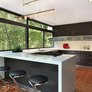 Modelo de cocina en U, minimalista, de tamaño medio, con suelo de baldosas de terracota, fregadero bajoencimera, armarios con paneles lisos, puertas de armario de madera en tonos medios, encimera de cuarzo compacto, salpicadero verde, salpicadero de azulejos en listel y península