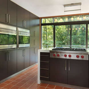 Mid-sized modern enclosed kitchen pictures - Enclosed kitchen - mid-sized modern l-shaped terra-cotta floor enclosed kitchen idea in Providence with stainless steel appliances, an undermount sink, flat-panel cabinets, dark wood cabinets, quartz countertops and no island