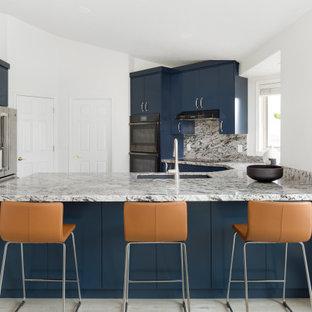 Diseño de cocina en U, moderna, de tamaño medio, con despensa, fregadero bajoencimera, armarios con paneles lisos, puertas de armario azules, encimera de granito, salpicadero multicolor, electrodomésticos de acero inoxidable, suelo laminado, península, suelo gris y encimeras multicolor