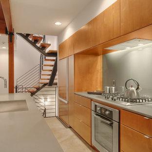 Diseño de cocina de galera, moderna, con electrodomésticos de acero inoxidable, armarios con paneles lisos, puertas de armario de madera oscura, salpicadero verde y salpicadero de vidrio templado